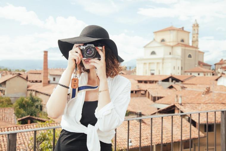djevojka sa šeširom drži fotoaparat