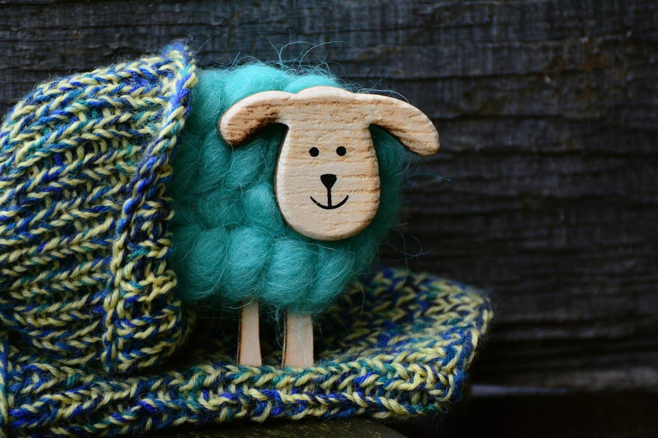 Pletene šarene čarape i napravljena ovca od drveta i vune