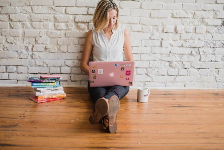 Žena sa laptopom sjedi na podu