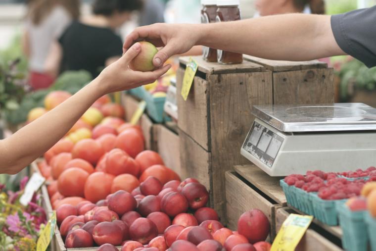 Prodavac daje jabuku kupcu na pijaci