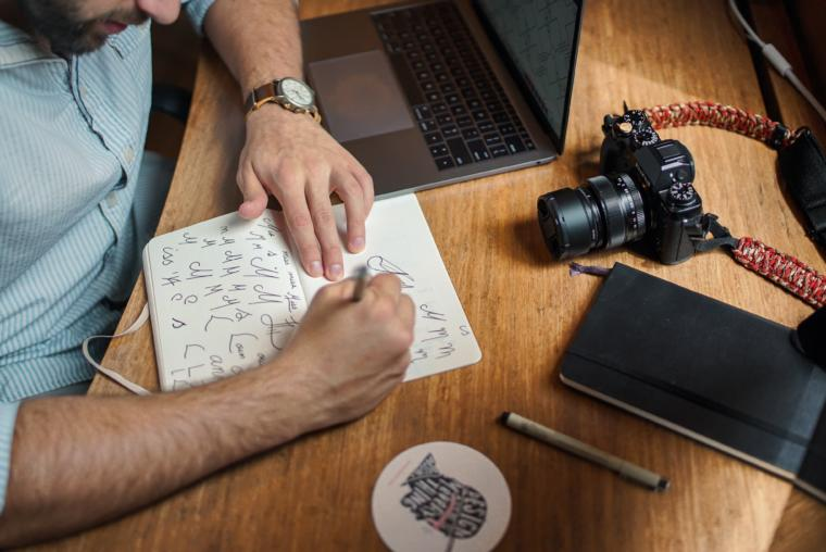 Čovjek piše za stolom kraj laptopa i fotoaparata
