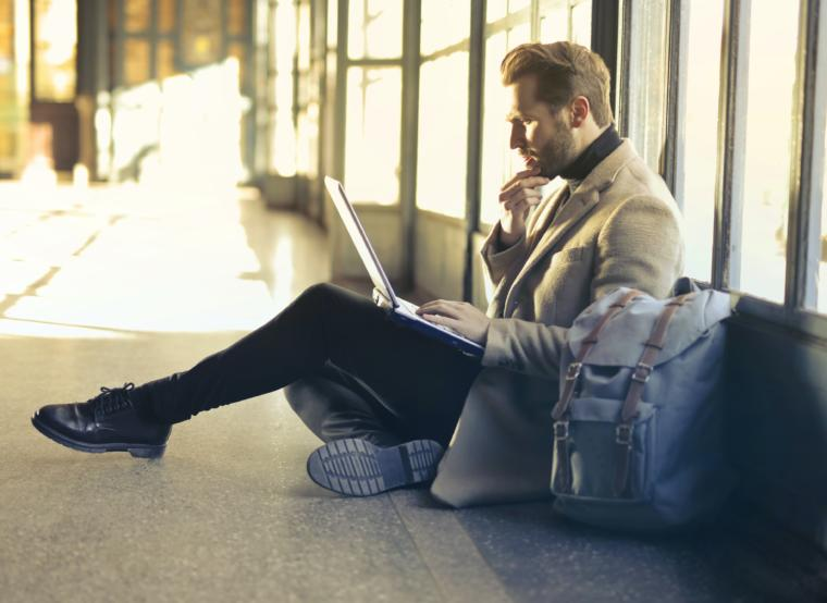 Čovjek gleda u laptop i sjedi kraj prozora