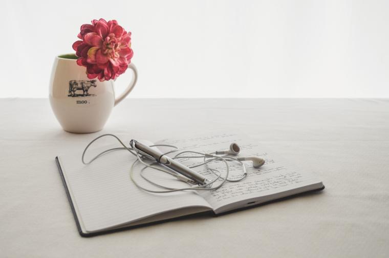 sveska sa olovkom i slušalicama i šolja sa cvijetom