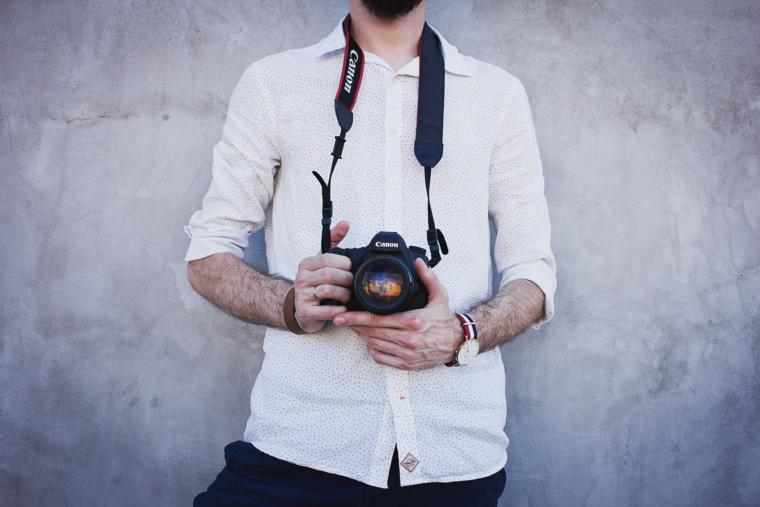 muškarac nosi fotoaparat na vratu