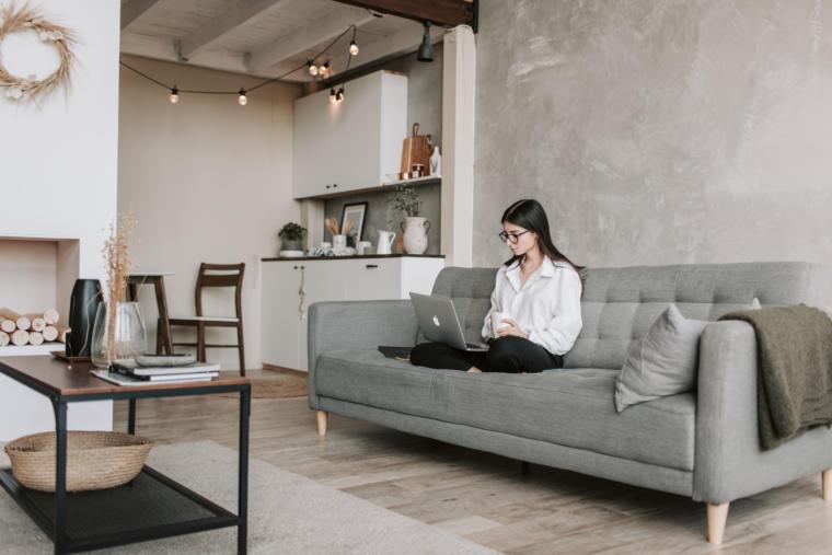 djevojka sjedi u dnevnoj sobi sa laptopom