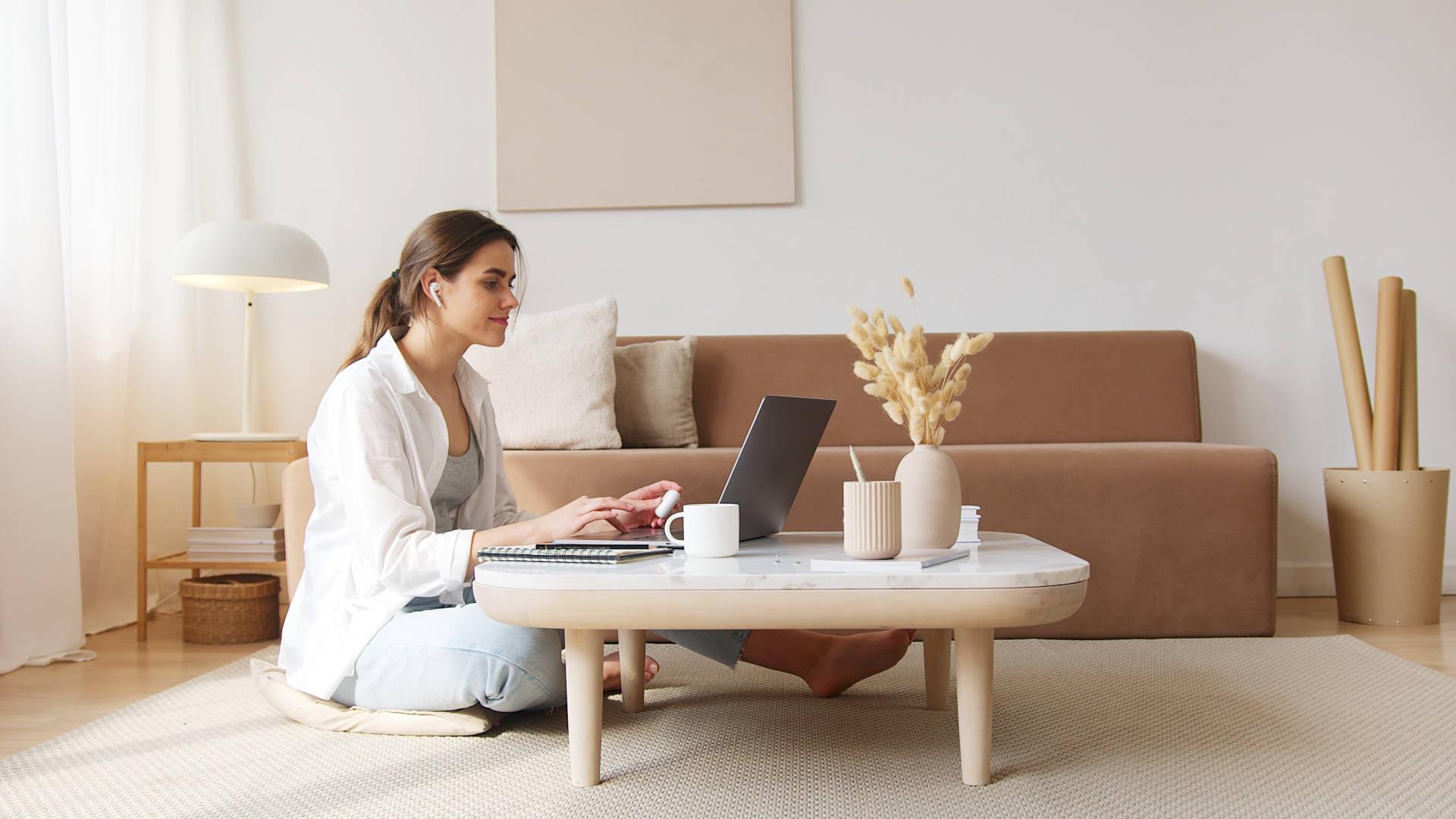 Žena sjedi za stolom i uči sa laptopa