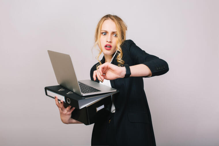 Djevojka drži laptop i gleda na sat