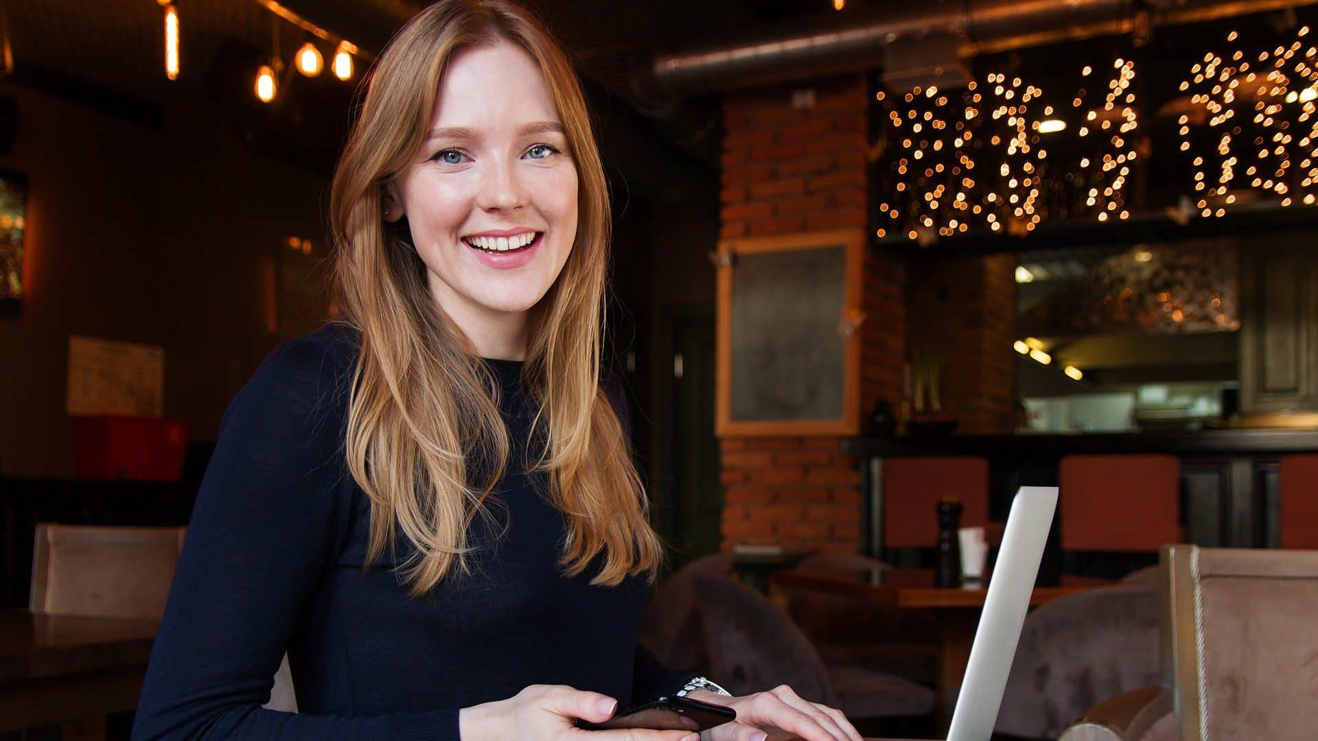 Nasmijana djevojka za laptopom i mobitelom u ruci
