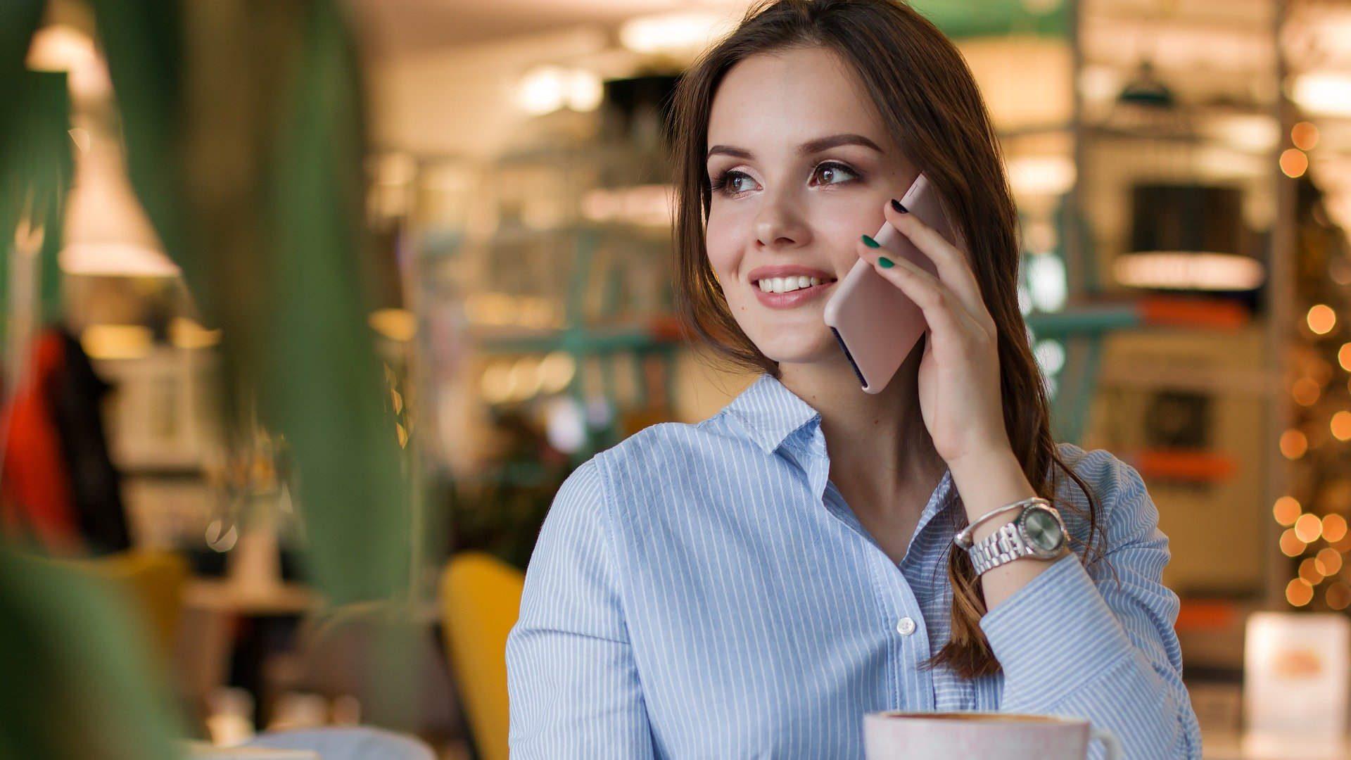 Nasmijana djevojka razgovara mobitelom